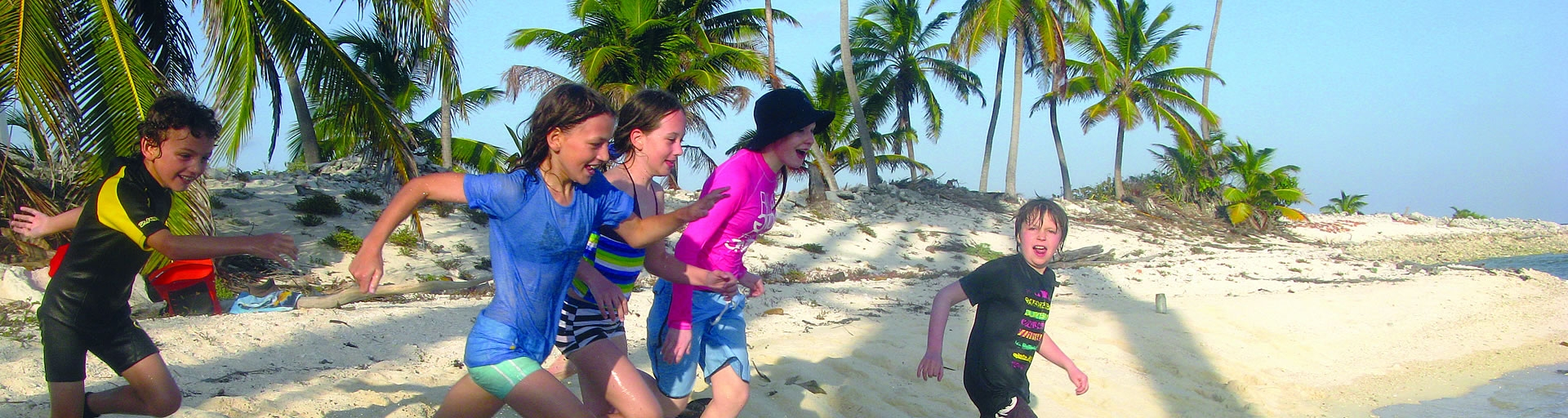 kids running on the beach in belize
